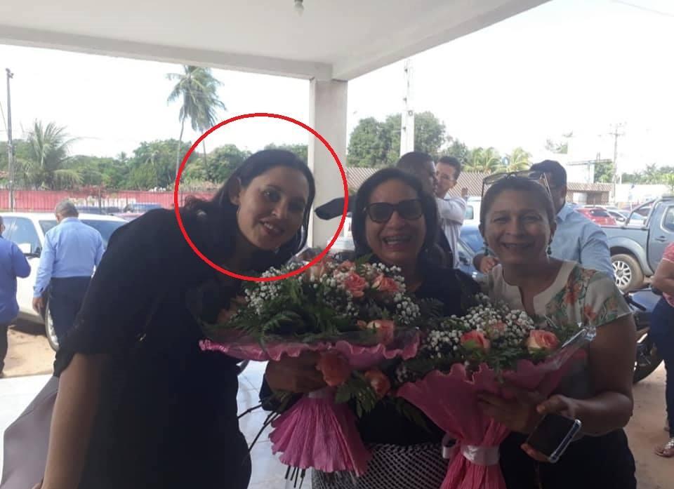 Na imagem, a professora da rede pública municipal de ensino aparece presenteando a prefeita do PCdoB com buquê de flores...